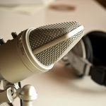 Microphone with headphones in the background ready for podcast recording