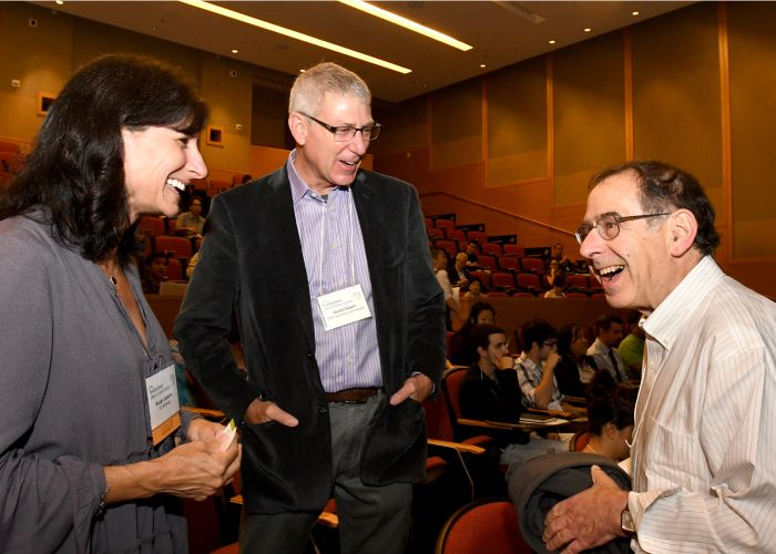 Three people laughing at the Rewriting Genomes Symposium