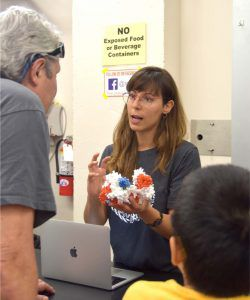 Scientist holding a 3D printed model of a protein and talking