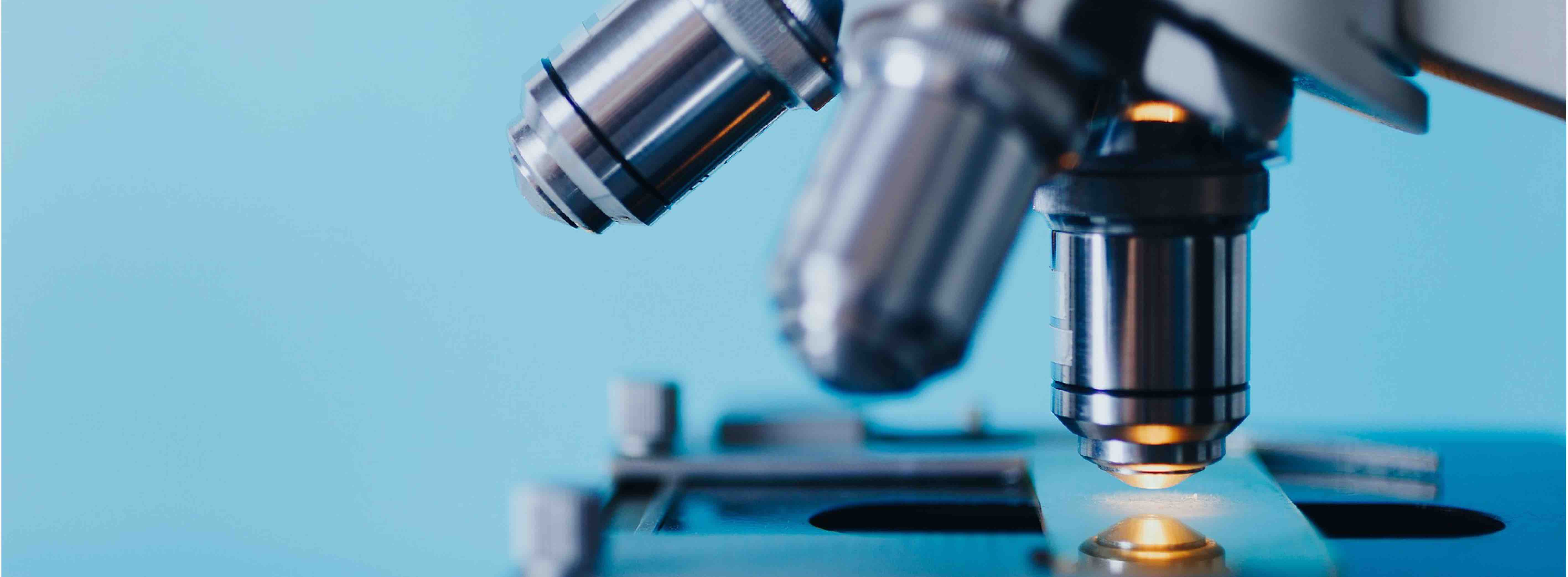 Image of a microscope in front of a blue background