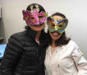 Two scientists wearing Mardi Gras masks