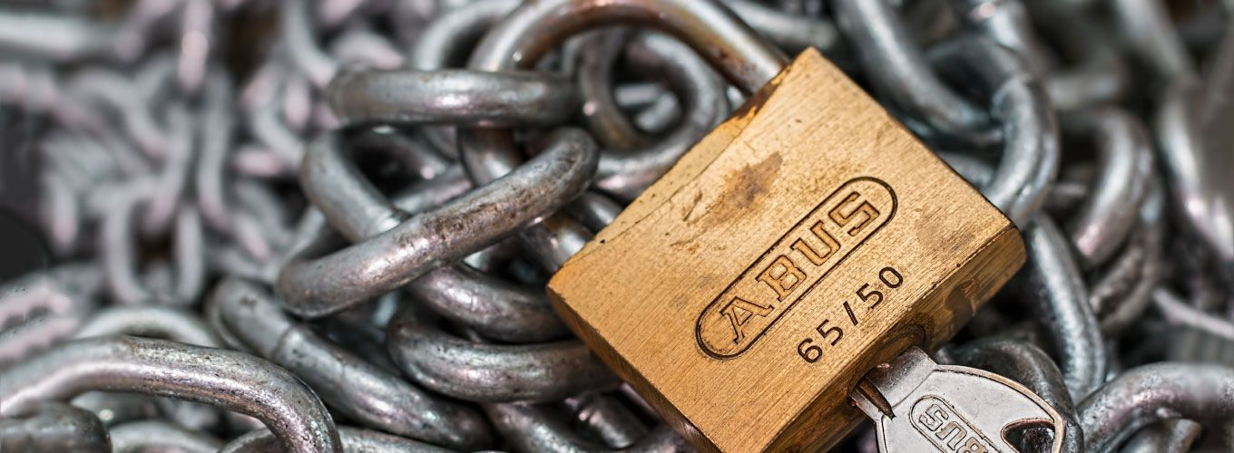 A padlock and key sitting on chains
