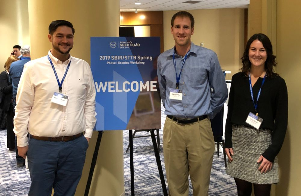 Three people standing in front of a welcome sign at a conference