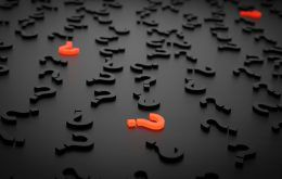 Many dark question marks scattered on a surface with three illuminated