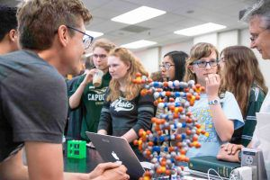 Students standing behind a toy model of DNA