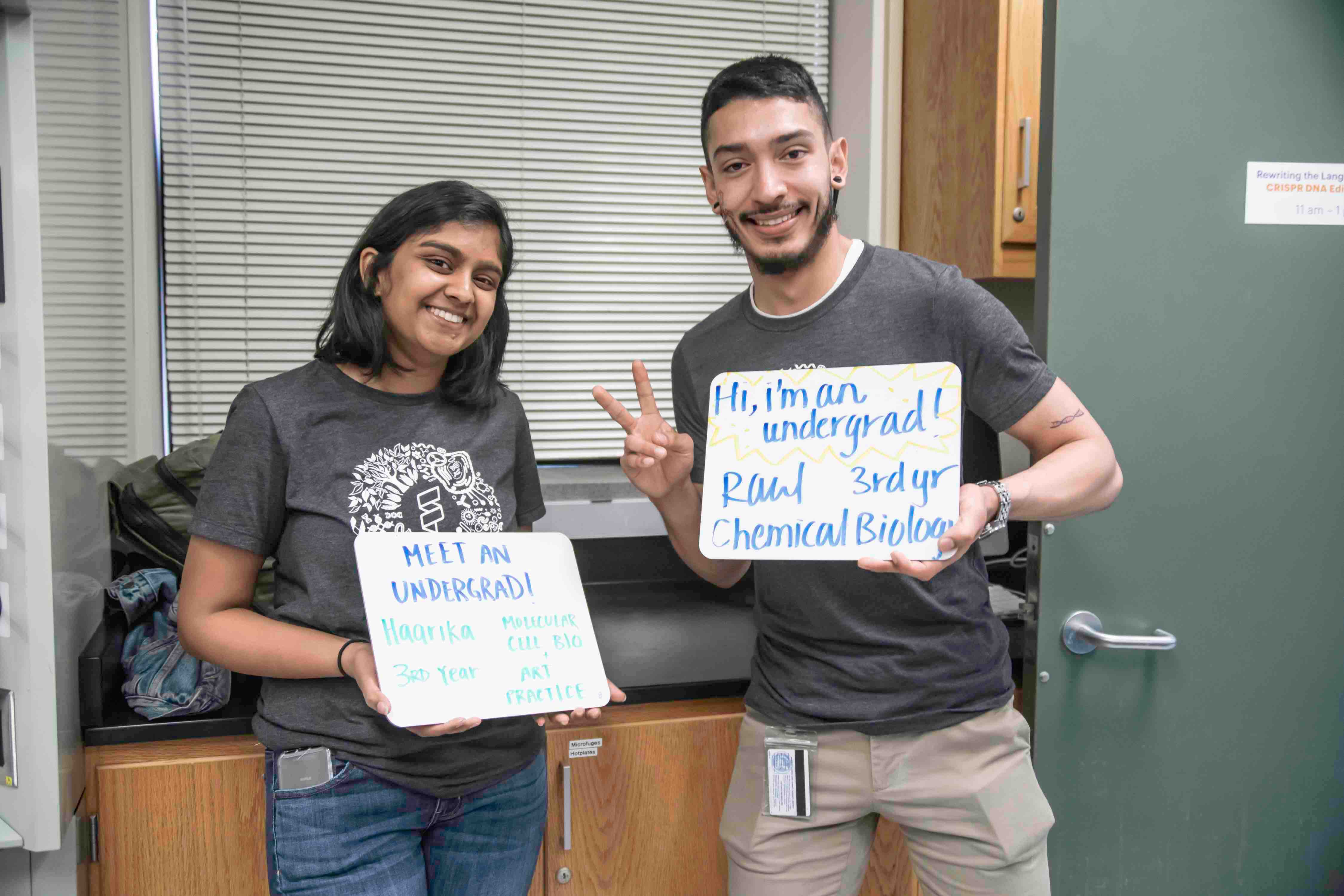 Two undergraduate students holding whiteboard signs