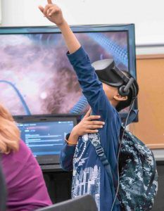 Child pointing upwards with a virtual reality headset on