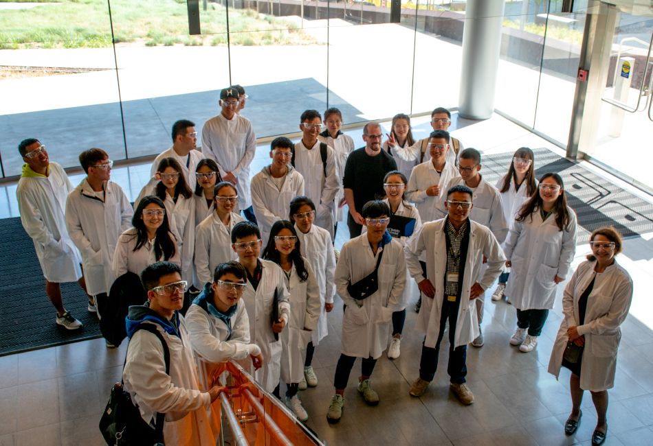 A group of students in lab coats standing in a lobby