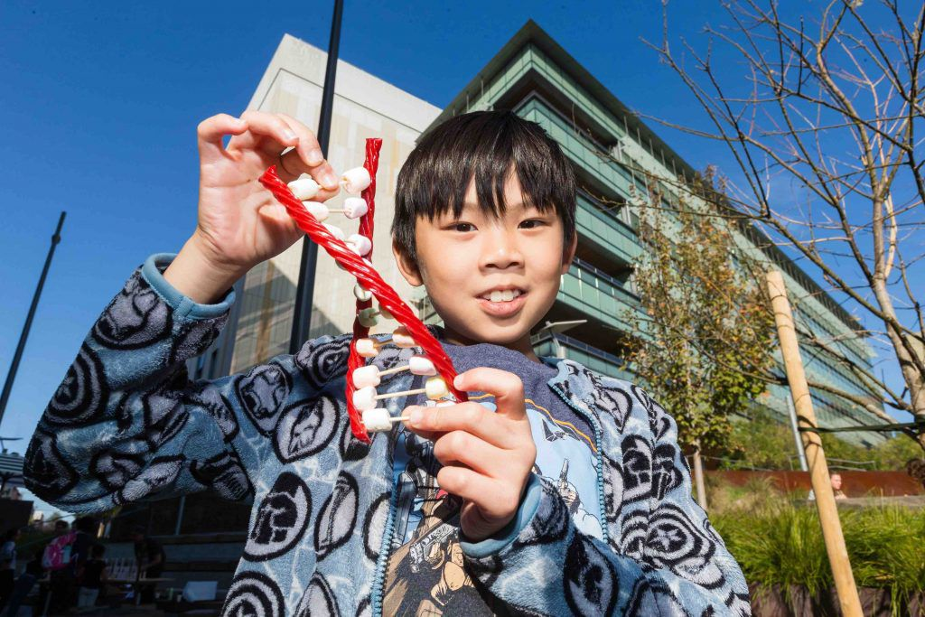 photo of a child holding a candy model of DNA