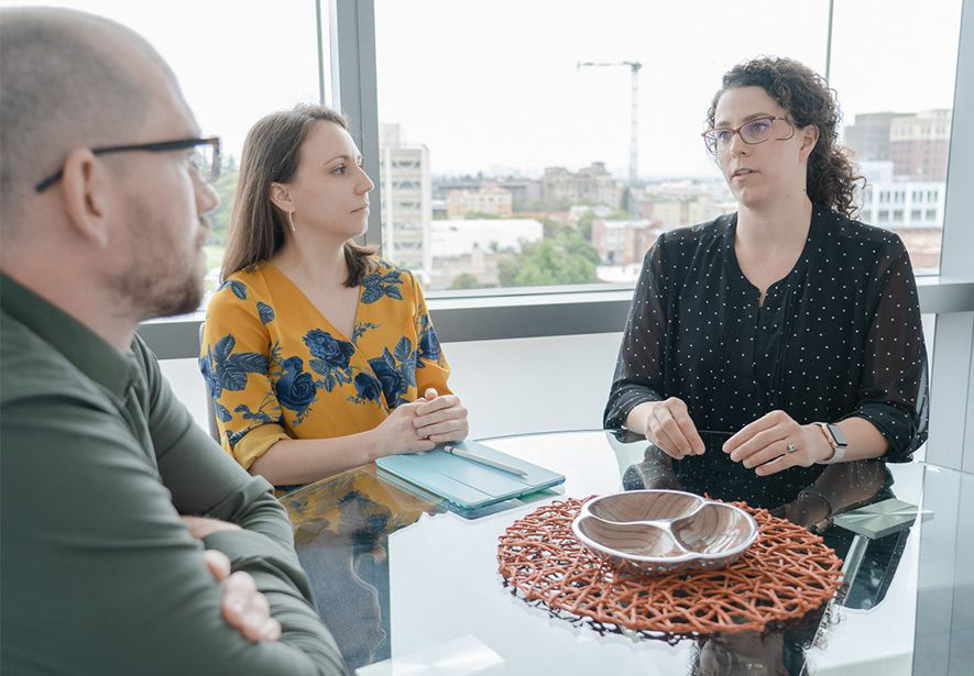 Three people having a discussion around a table