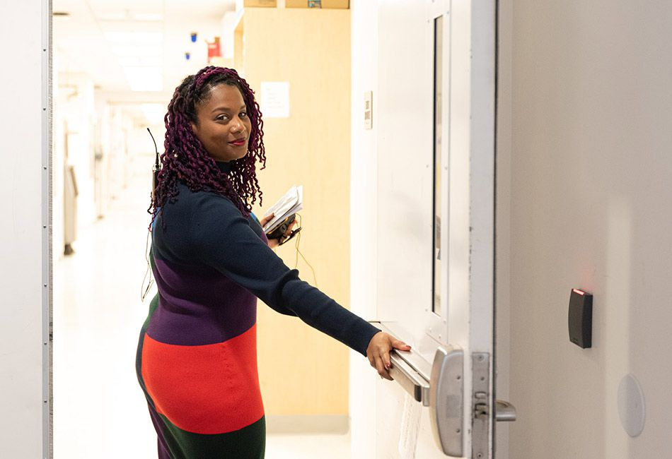 A woman opening a door, leading a field trip