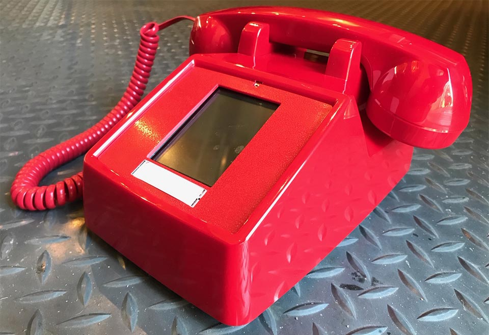 A vintage, red dial phone with a touch screen in place of the rotary dial