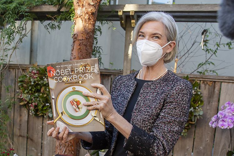 Photo of Jennifer Doudna holding up the Nobel Prize Cookbook