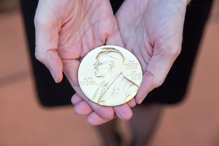 Closeup of the gold Nobel Prize medal in Jennifer Doudna's hand