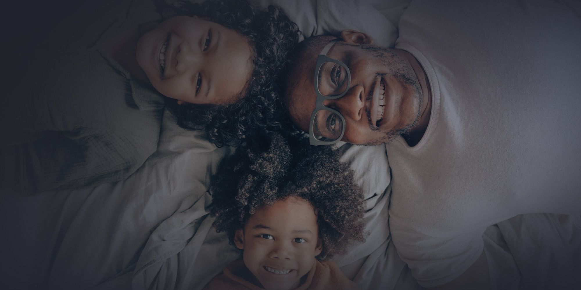 Black father smiling with Black children